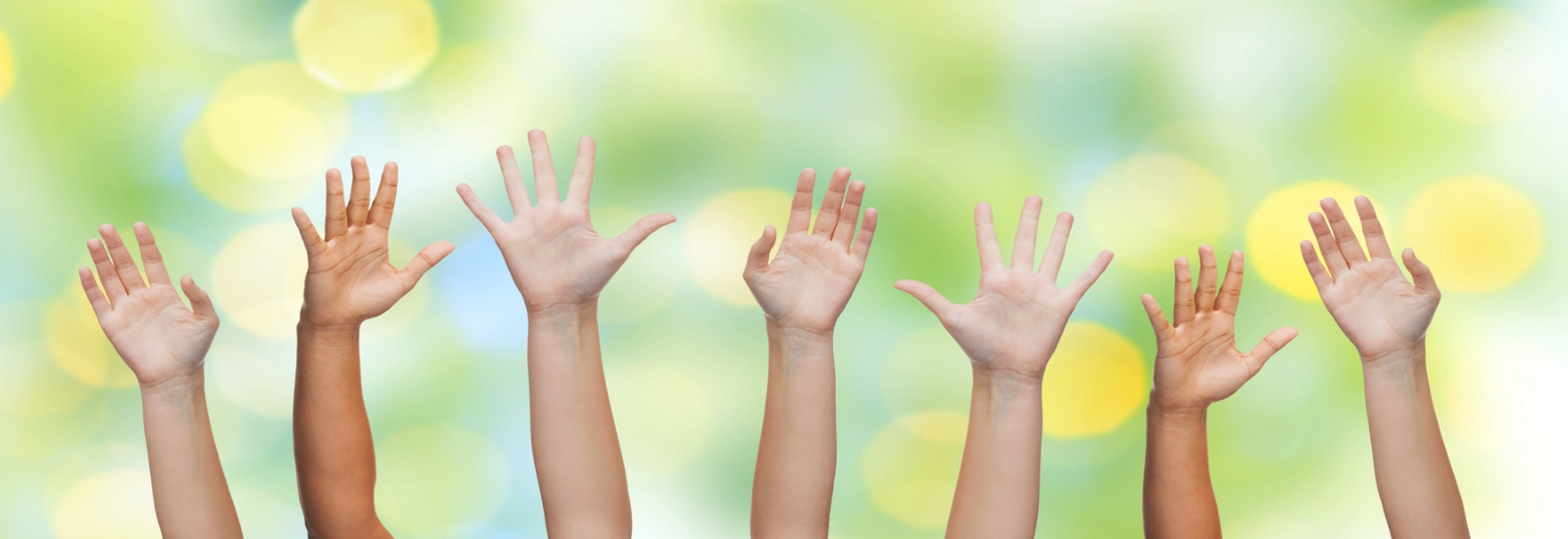 Children's hands raised in the air to answer questions.