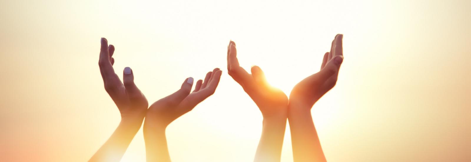 Hands raised in prayerful gesture.